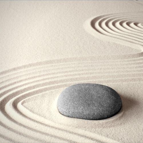 Foto de uma pedra ao lado de uma série de linhas dispostas em formato sinuoso feitas em areia branca.