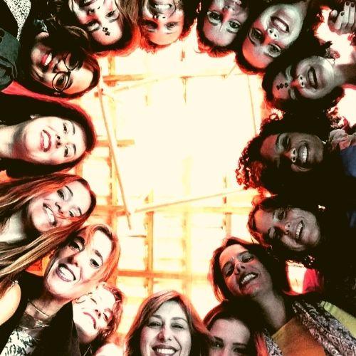Foto de mulheres abraçadas em círculo. Elas sorriem e olham pra baixo.