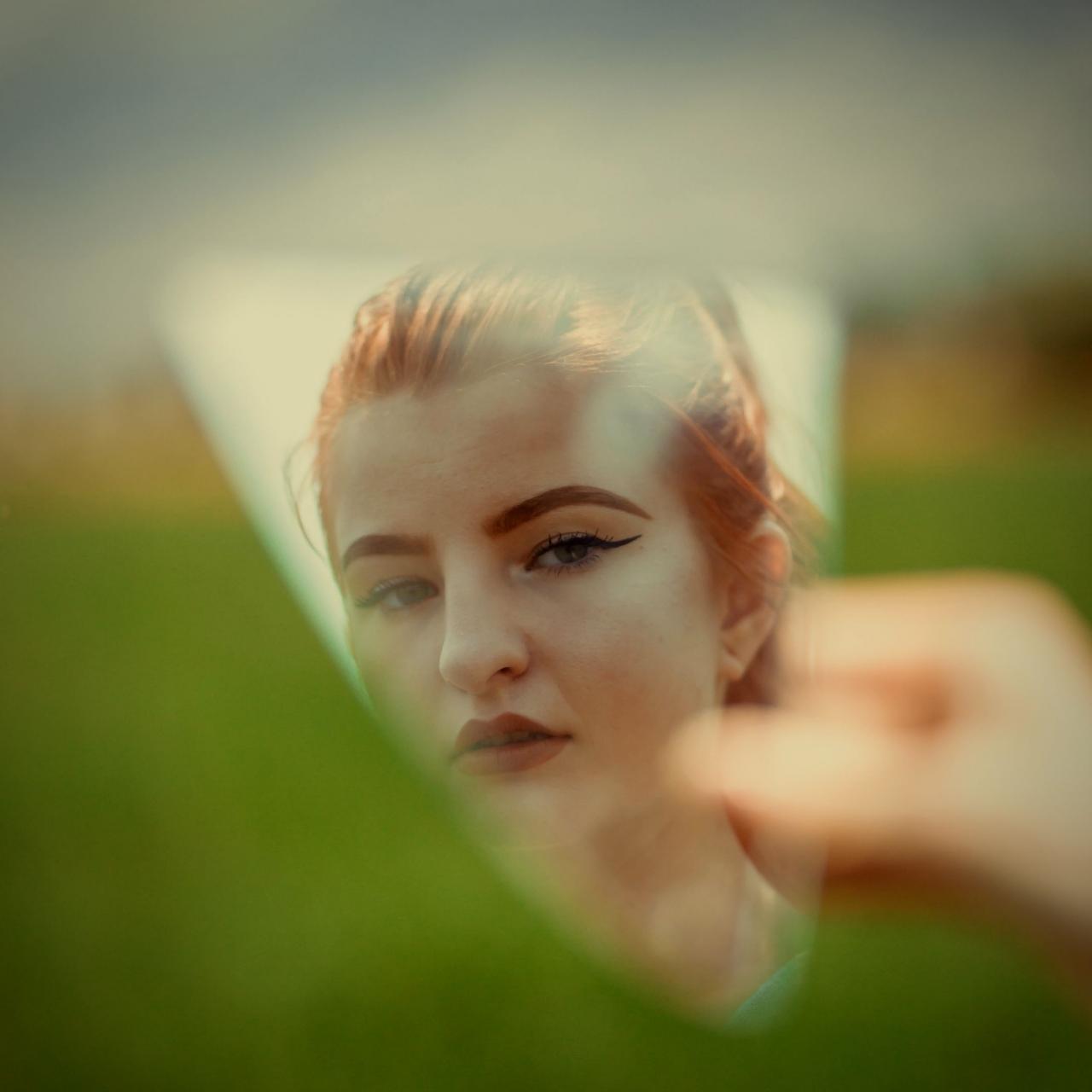 Foto do reflexo de mulher séria em um pedaço de espelho. Ela é ruiva e está com os cabelos presos para trás. Ao redor, toda a imagem está desfocada.