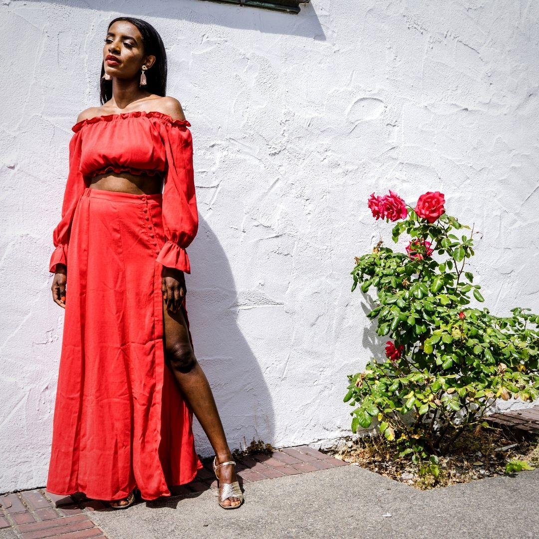 Foto de mulher negra em pé em uma área externa em um dia ensolarado. Ela usa uma blusa e saia longa na cor vermelha. Ao lado dela, há arbusto com flores.